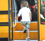 A little boy climbs the steps to get on his school bus.