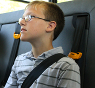 A boy sits on the school bus wearing a SafeGuard seat belt.