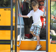 A young boy gets off his school bus.