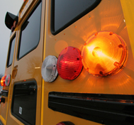 Lights blink on a stopped school bus.