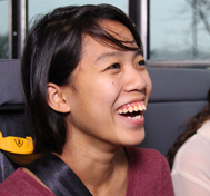 A female high school students laughs while buckled into her SafeGuard seat belt.