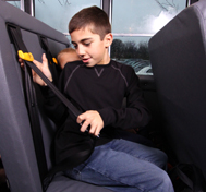 A young boy buckles up in his SafeGuard seat belt on the school bus.