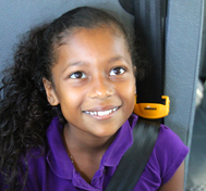 A young girl smiles at the camera while buckled in to her SafeGuard seat belt.