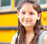 A smiling girl stands in front of her school bus.