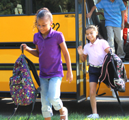 Students get off their school bus.