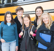 Teenagers smile for the camera while standing in front of their school bus.