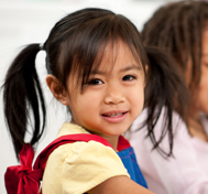 A young girl with pigtails smiles at the camera.