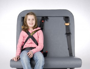 A young girl sits on her school bus seat wearing the SafeGuard Upper Torso Control device.