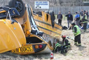 Photo of Griffith High School School Bus on its roof after a rollover.